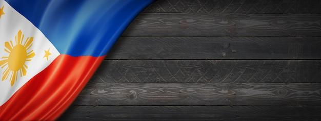 Philippines flag on black wood wall. horizontal panoramic banner.