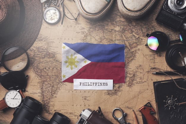 Philippines flag between traveler's accessories on old vintage map. overhead shot