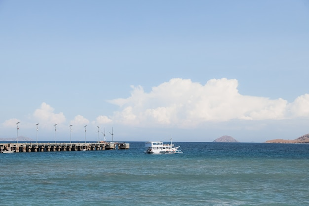 Phinisi boat sailing on the sea passing the pier