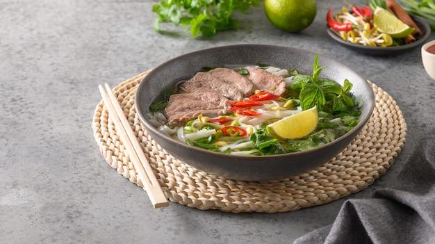 Суп фо бо с говядиной в серой миске на серой вьетнамской кухне