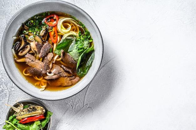 Pho bo вьетнамский суп из свежей рисовой лапши с говядиной, зеленью и чили. белый фон. вид сверху. копировать пространство