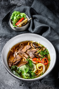 Pho bo  vietnamese fresh rice noodle soup with beef, herbs and chili. black background. top view