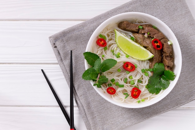 Pho bo - vietnamese fresh rice noodle soup with beef, herbs, lime and chili. vietnamese national dish.