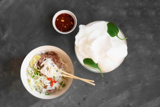 灰色の背景に牛肉とライスチップスとゴマソースの伝統的なスナックを添えたフォーボーベトナムヌードルスープ