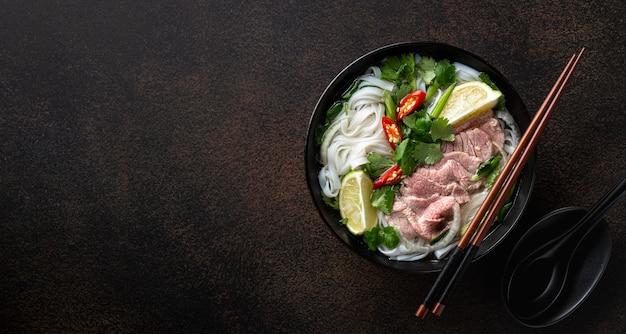 어두운 배경, 평면도, 복사 공간에 쇠고기와 쌀 국수와 포 보 베트남 수프