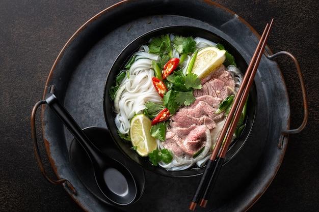 어두운 배경에 쇠고기와 쌀 국수와 포 보 베트남 수프, 상위 뷰