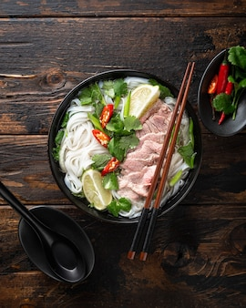 Pho bo vietnamese soup with beef and noodles on a wooden table, view from above