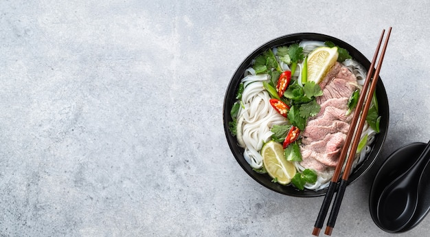 Pho bo vietnamese soup with beef and rice noodles on concrete background, top view, copy space