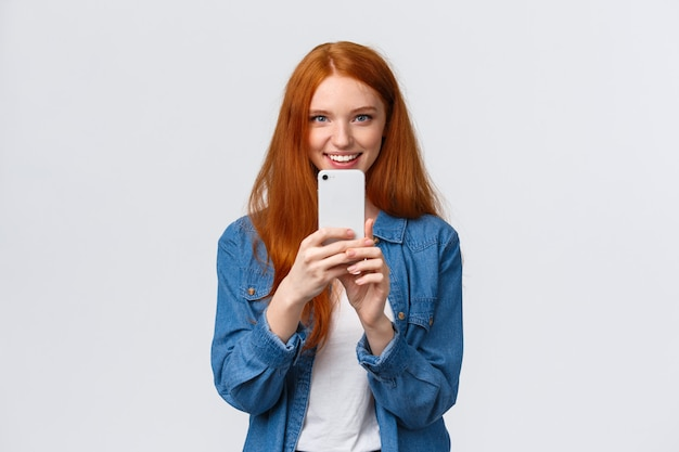友情、一体感、現代のライフスタイルコンセプト。かわいい赤毛の女の子が完璧な角度を検索、スマートフォンで友人のショットを撮る、phogotaphing、面白いものを撮影する