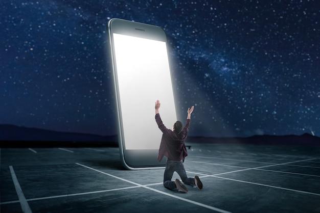 電話中毒の人々の概念。画面が光る大型スマートフォンにひざまずいて祈る男。スケーリング効果