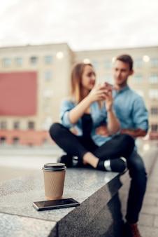 電話中毒のコンセプト、スマートフォン、コーヒー。社会中毒の人々、若者はガジェットなしでは生きられない