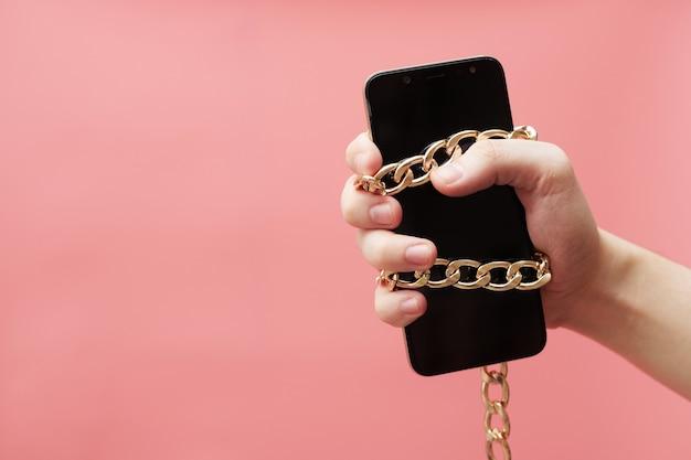 Телефонная зависимость, концепция социальных сетей, привязанная к руке с цепочкой смартфона на розовом фоне. фото высокого качества