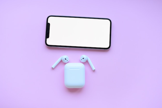 Phone and air pods and pencil on pink background