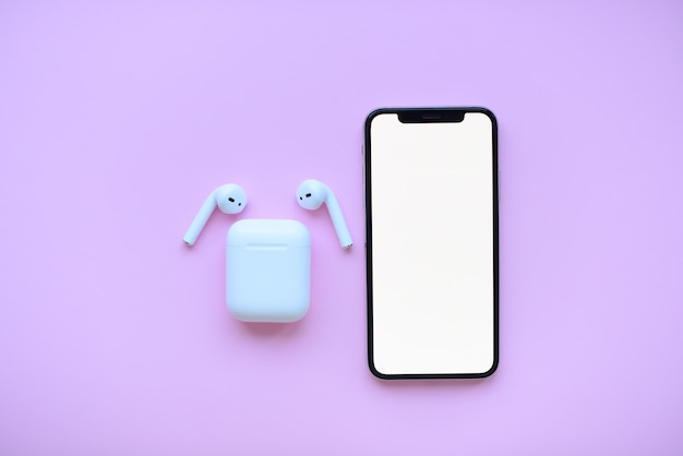 Phone and air pods on pink background