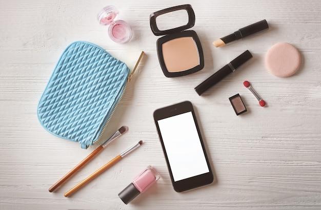 電話と木製のテーブルの化粧品