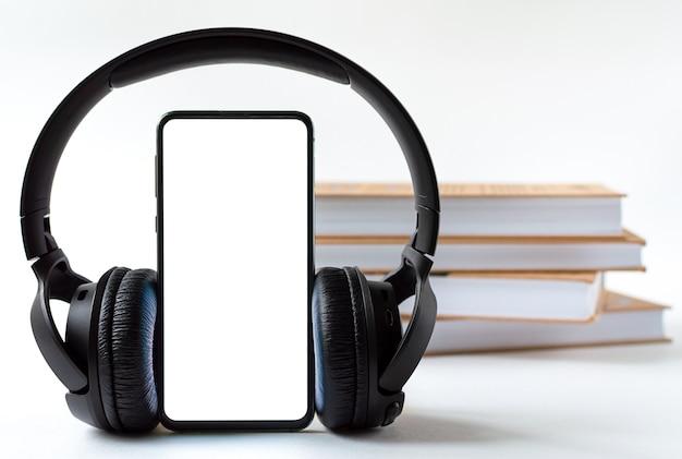本の背景にある電話とヘッドフォン。テクノロジーまたはクラシックのコンセプトの選択。