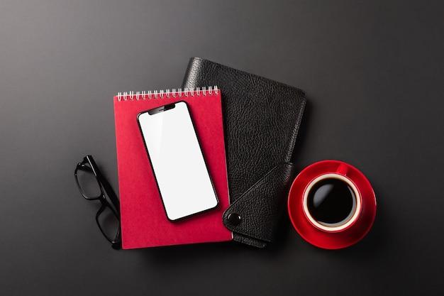 一杯のコーヒーと一緒にデスクトップ上の電話とメモ帳は、ソーシャルネットワークで働き、メモ帳に書き込みます。上からの眺め。高品質の写真