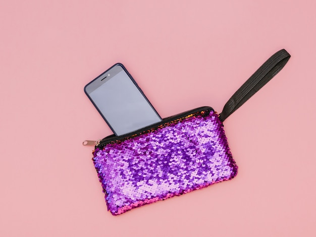 전화 및 분홍색 배경에 빛나는 보라색 여자의 핸드백. 평평하다.