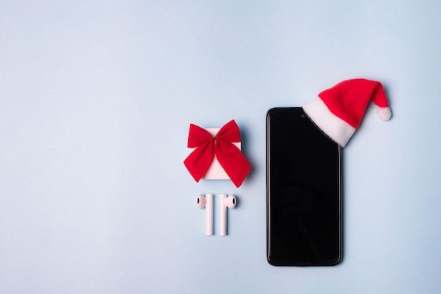 백그라운드에서 전화 및 무선 헤드폰. 산타 모자에있는 새해 선물. 상위 뷰의 레이아웃입니다. 현대 기술. 헤드폰의 음악. 휴가를위한 선물. 공간 복사