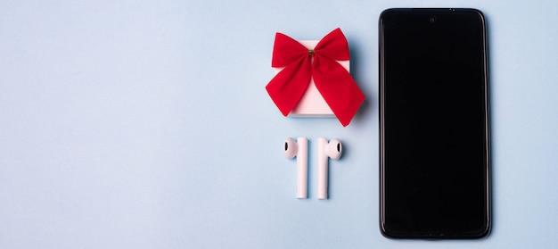 電話とワイヤレスヘッドホン。上面図のレイアウト。現代のテクノロジー。ヘッドホンの音楽。休日への贈り物。