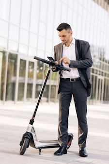 Phone application for rental scooter ecological city transport businessman rents electric scooter us...