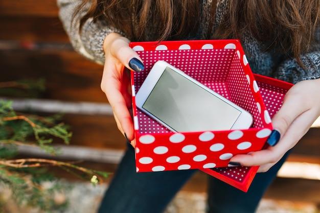 Telefono come regalo di natale nella casella rossa di natale nelle mani di una bella ragazza.