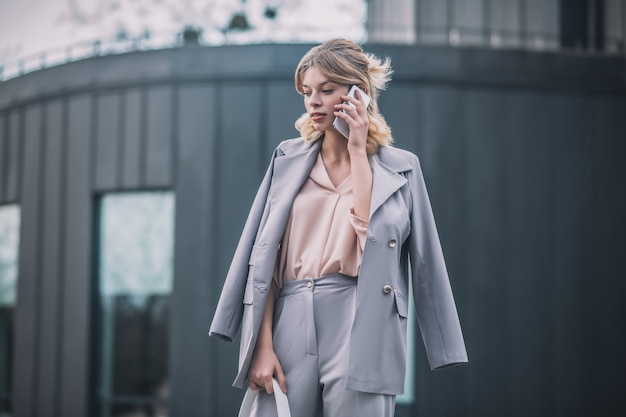 電話。ハンドバッグと路上で彼女の耳の近くにスマートフォンとビジネス灰色のスーツの美しい若い穏やかな女性