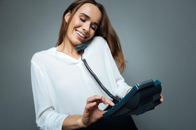 Телефонный звонок. обрадованная позитивная милая женщина держит в руках проводной телефон и прижимает трубку плечом при наборе номера.