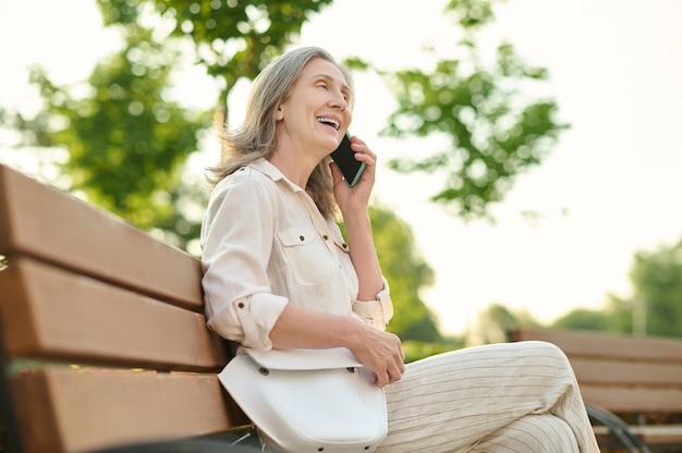 전화. 공원 벤치에 앉아 스마트폰으로 이야기하는 핸드백을 들고 정년의 즐거운 성인 여성