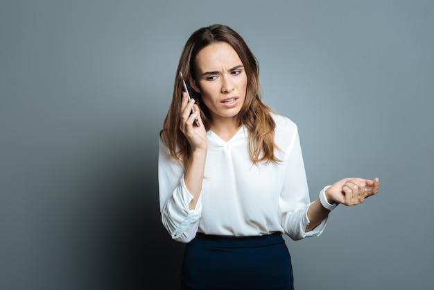 電話。スマートフォンを耳に当て、電話で会話しながら対話者の話を聞く、気持ちのいい不機嫌そうなスマート実業家