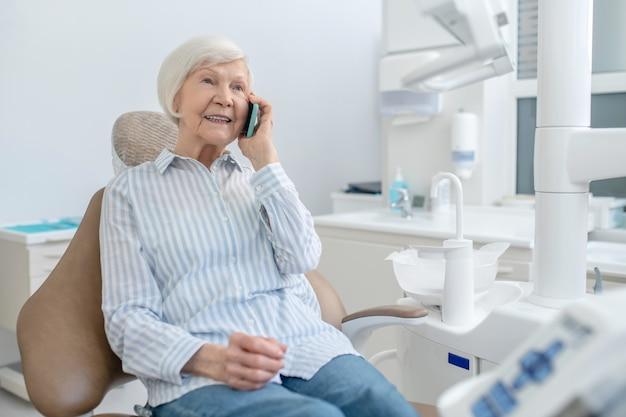 電話。歯科医院に座って電話で話している年配の女性