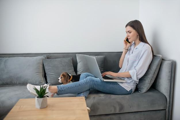 Телефонный звонок. молодая темноволосая женщина сидит со щенком и разговаривает по телефону