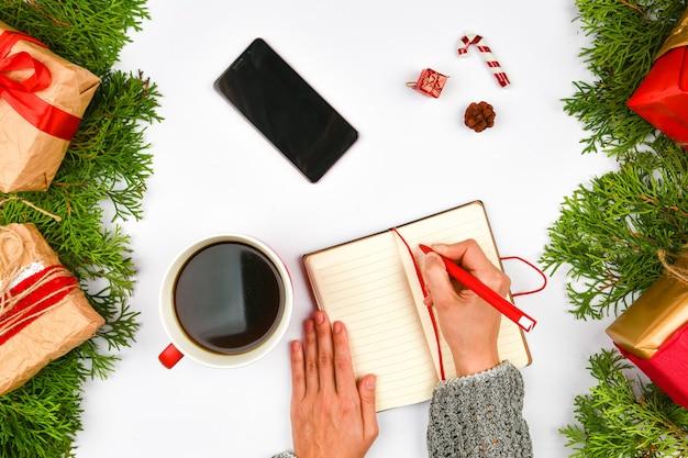 Телефон, кофейная кружка на рождественском пространстве. вид сверху. место для письма. пустое пространство. уютный отдых. кружка латте, блокнот, ручка, телефон, подарочная упаковка. иглы.