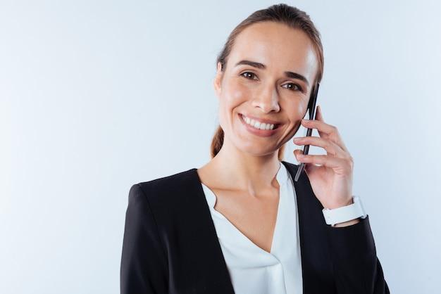 Телефонная связь. позитивная восхищенная приятная женщина улыбается и держит свой смартфон во время звонка