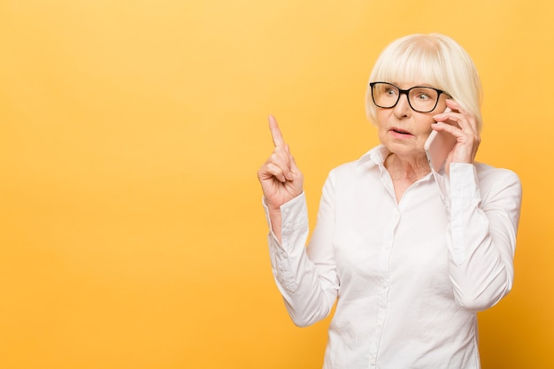 Phone conversation. aged woman while talking on the phone isolated over yellow background.