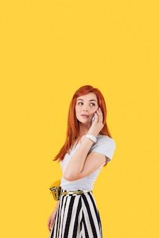 電話での会話。電話で会話しながら電話を耳に当てる魅力的な若い女性