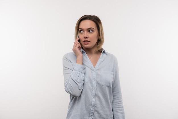 전화 통화. 흰색 배경에 서있는 동안 전화로 이야기하는 즐거운 좋은 여자