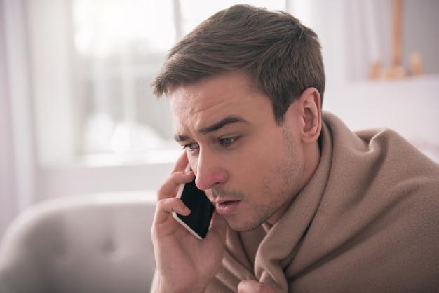電話での会話。電話で会話しながら電話を耳に押し付ける素敵なハンサムな男の肖像画
