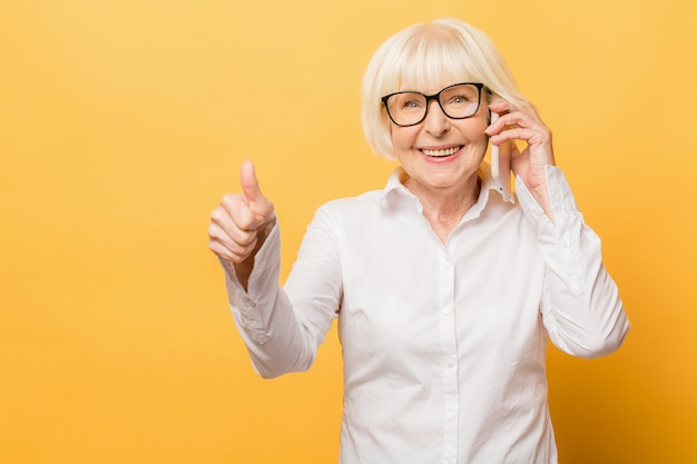 Phone conversation. positive aged woman smiling while talking on the phone isolated over yellow background. thumbs up.