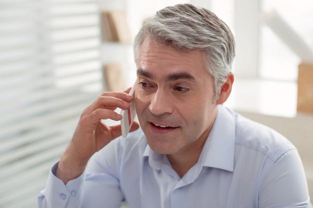 電話での会話。彼の電話を耳に置き、仕事について話している間話している賢い楽しい前向きな人
