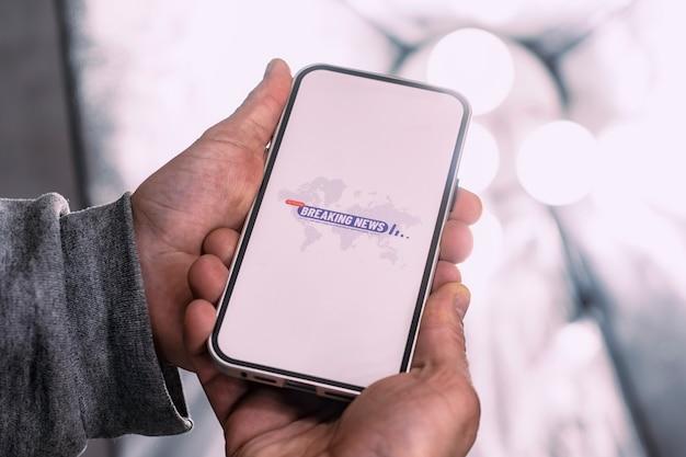스튜디오 조명을 배경으로 설정된 속보 아이콘이 있는 전화기 디스플레이. 한 남자가 손 클로즈업에 스마트폰 모형을 들고 있습니다.