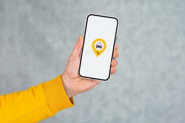 밝은 배경에 택시 아이콘이 있는 전화 디스플레이. 남자는 그의 손 클로즈업에 모형 스마트폰을 보유하고 있습니다.