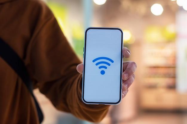 상점 창을 배경으로 wi-fi 아이콘이있는 휴대폰 디스플레이