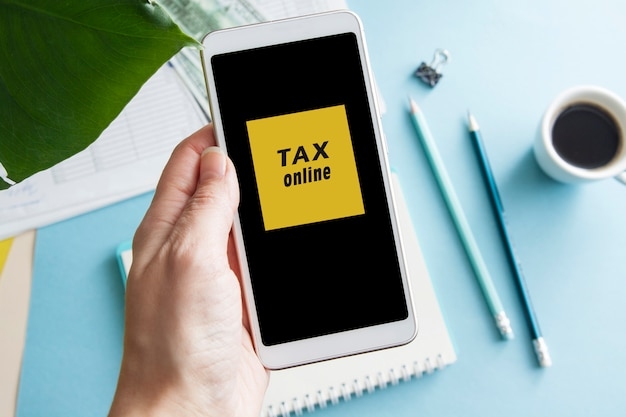Phone in a female hand with online taxes program