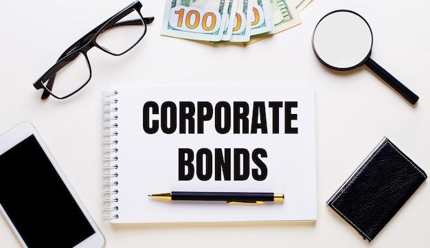 Телефон, очки, лупа, деньги, блокнот с текстом корпоративные облигации и ручка на светлом столе. бизнес-концепция