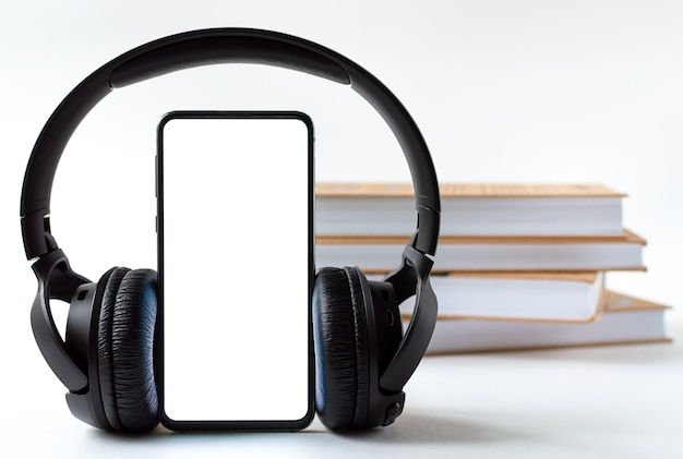Phone and headphones in the background of books. concept choice of technology or classics.