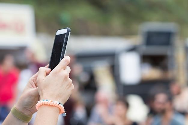Телефон в руке, чтобы сфотографировать над толпой