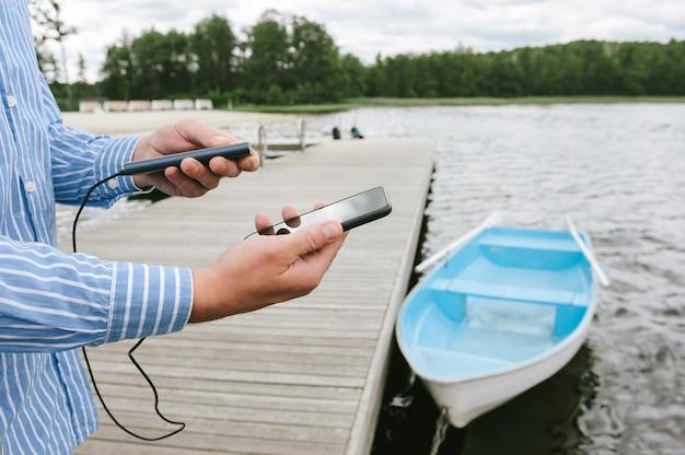 손에 전화 전원 은행 충전기와 남자입니다. 물과 부두에 보트의 배경. 여행을 주제로 한 개념입니다.