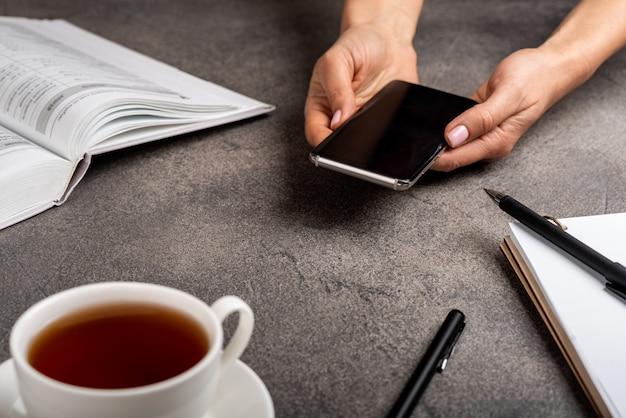 Телефон в руках женщины с книгой, блокнотом, ручками и чашкой чая