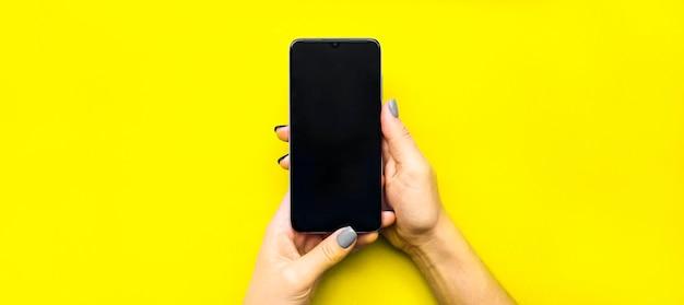 План телефона. девушка держит телефон обеими руками. желтый фон, серый маникюр. красивый маникюр. плоская планировка. цвет 2021 года.